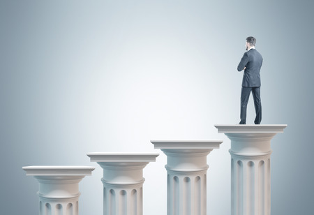 Rear view of a businessman looking at a blank gray wall standing on a tall Greek column. 3d rendering mock up Stock Photo