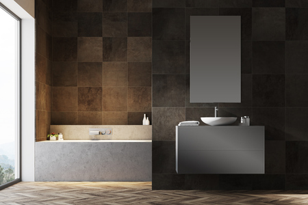 Dark tiled bathroom interior with a wooden floor, a bathtub, a sink on a gray vanity unit and a narrow vertical mirror. 3d rendering mock up