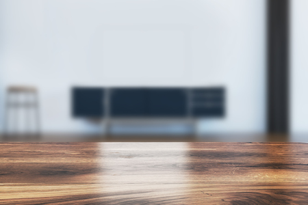 White living room interior with a black and wooden cabinet, a stool standing near it and a table in the foreground. 3d rendering mock up blurred Stock Photo