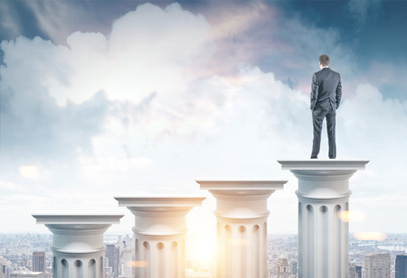 Rear view of a businessman looking at a cityscape standing on a tall Greek column. 3d rendering mock up