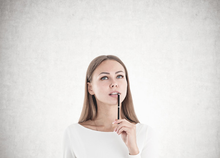 Attractive young woman with fair hair wearing white is holding a pen near her full lips, looking up and thinking. A concrete wall background.