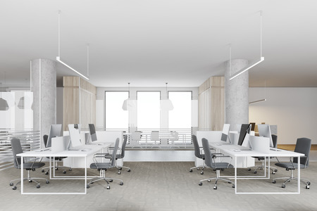 Computer monitors standing on white office tables in a room with white walls, a concrete floor and columns. A side view. 3d rendering mock up