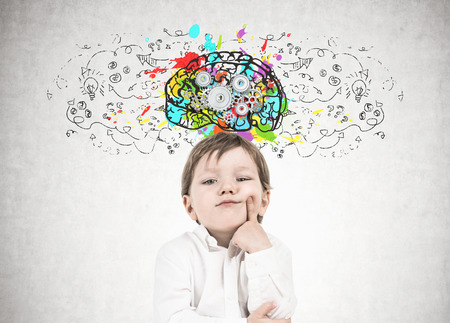 Cute little boy in a white shirt and dark blue jeans is thinking holding his finger near his cheek. Decision making concept. A concrete wall background with a cog brain sketch on it. Stock Photo - 96979402