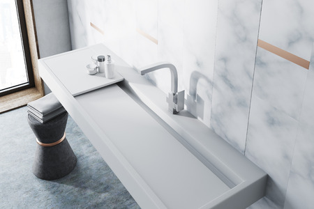 White marble wall bathroom interior with a long white sink and a chair with towels. A top view. 3d rendering Stok Fotoğraf