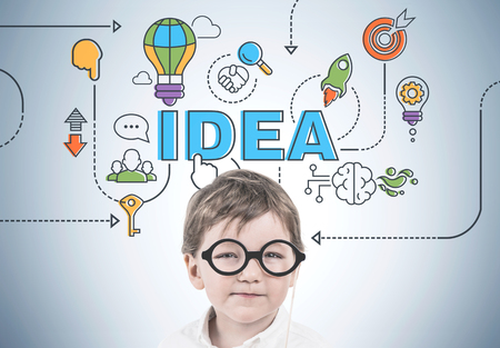 Cute little boy in a white shirt is wearing a pair of glasses with a thick frame and thinking while looking at camera. A gray wall with a business idea sketch