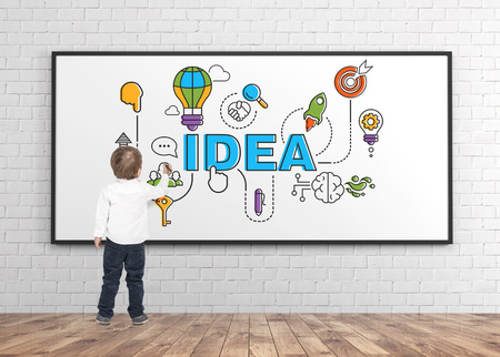 Rear view of a cute little boy wearing a white shirt and dark blue jeans writing or drawing with a marker. A whiteboard background with a good start up idea sketch