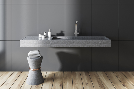 Gray wall bathroom interior with a long gray sink and a chair with towels. A front view. 3d rendering