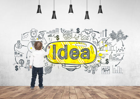Rear view of a cute little boy wearing a white shirt and dark blue jeans writing or drawing with a marker. A concrete wall with a business plan sketch and a large light bulb