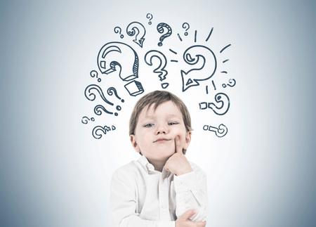 Un mignon petit garçon vêtu d'une chemise blanche et d'un jean bleu foncé pense à tenir son doigt près de sa joue. Concept de prise de décision. Un fond de mur gris avec de nombreux points d'interrogation Banque d'images