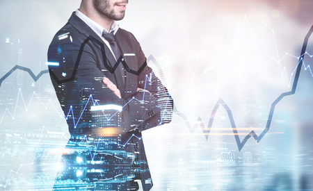 Side view of a pensive young businessman with a beard. He is wearing a suit and a tie and standing with crossed arms. Graphs. A night cityscape background. Toned image double exposure mock up