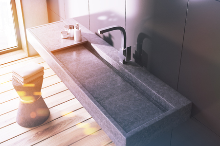 Gray wall bathroom interior with a long dark gray sink and a chair with towels. A top view. 3d rendering toned image double exposure Stock Photo