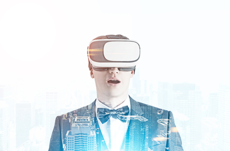 Astonished young businessman wearing a suit, a bowtie and VR glasses. Concept of the future technology. A cityscape background. Toned image double exposure