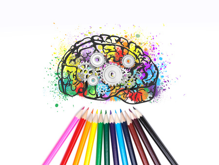Colorful brain sketch with gears on it. Different colored pencils lying under it. Creative thinking and design concept Foto de archivo