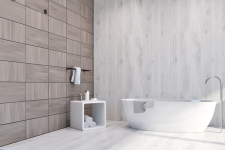 Luxury bathroom interior with tiled wooden walls, and a white bathtub standing in the corner. Chair with towels. 3d rendering mock up Фото со стока