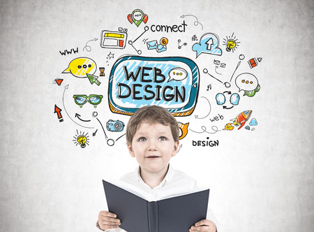 Portrait of a cute little boy in a white shirt holding an open book and looking upwards. A concrete wall with a web design sketch