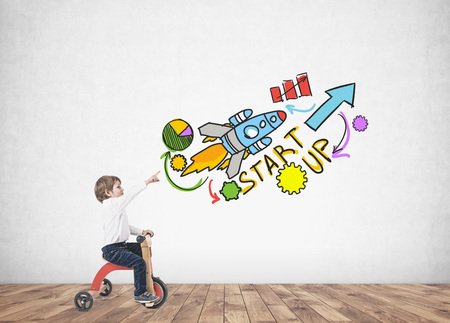 Cute little boy in a white shirt and dark blue jeans is riding a tricycle and showing with his finger. A concrete wall background with a start up sketch