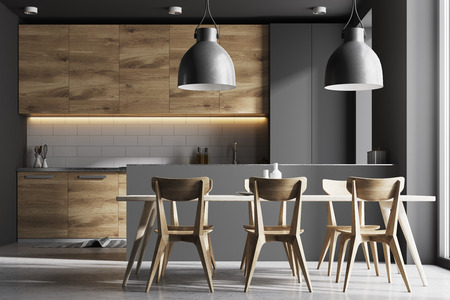 Modern kitchen interior with gray and white brick walls, a concrete floor and gray and wooden countertops. A long table with chairs near it. 3d rendering mock up