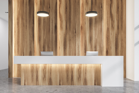 Close up of a wooden and white reception desk standing in a modern office hall with a concrete floor. 3d rendering mock up 写真素材