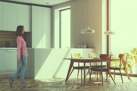 Modern kitchen interior with white and wooden walls, a wooden floor and white countertops. A long table with chairs near it. A side view. A woman. 3d rendering mock up toned image double exposure