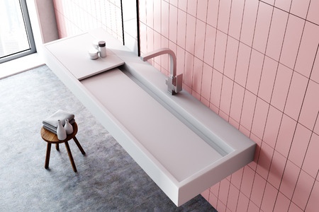 Modern sink in a pink tiled bathroom interior with a narrow vertical mirror and toiletry. A top view. 3d rendering mock up