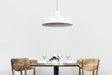 Round Wooden Table With Chairs Standing Near It And A Stylish Ceiling Lamp  Hanging Above It
