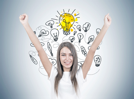 Smiling young woman with brown hair wearing a white t shirt is standing with her hands in the air and looking at the viewer. Yellow light bulbs on a gray wall. An idea concept