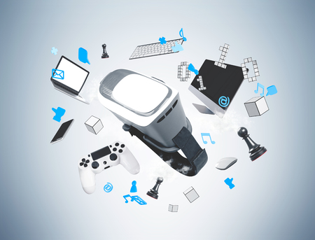 Virtual reality gadgets and compuaters floating in the air against a gray wall background. Mock up Stock Photo