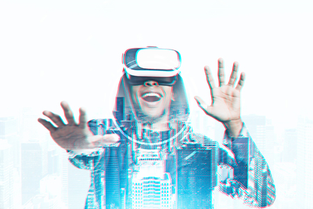 Happy young African American man wearing a hoodie and VR glasses. Concept of the future technology. A cityscape background. Toned image double exposure Stock Photo