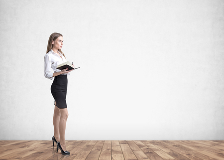 Side view of a blonde businesswoman wearing a white blouse, a black skirt and high heels shoes and holding a copybook. A concrete wall background. Mock up