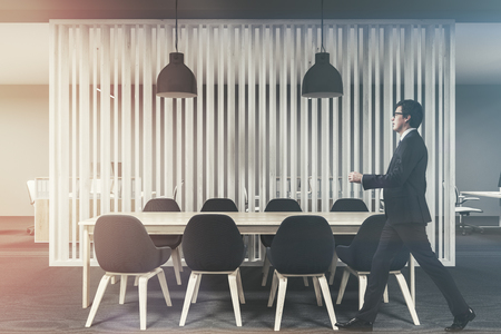 Wooden conference room interior with a concrete floor and a long wooden table with black chairs standing around it. A businessman walking. 3d rendering toned image Stock fotó
