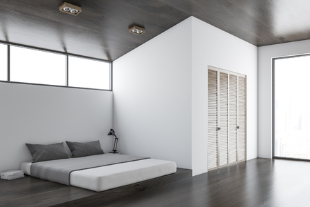 White wall bedroom interior with a concrete floor, a king size bed and a wardrobe. 3d rendering mock up
