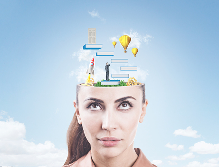Portrait of a serious young businesswoman looking upwards at education icons emerging from her head. A sky with clouds background. Standard-Bild