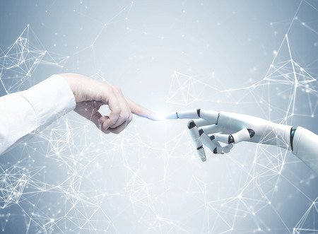 Human and robot hands reaching out and touching with index fingers. A gray background with a network hologram. Concept of hi tech Foto de archivo