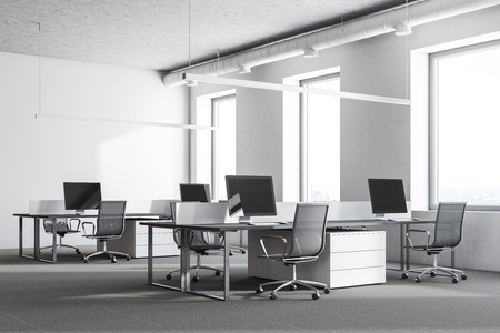 Modern office corner with white walls, loft windows, a carpet on the floor and rows of computer tables. 3d rendering mock up
