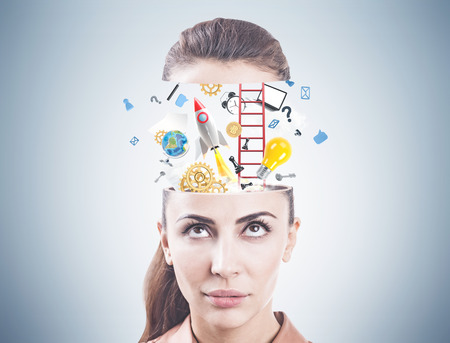 Portrait of a serious young businesswoman looking upwards at star up icons emerging from her head. A gray wall backgraound.