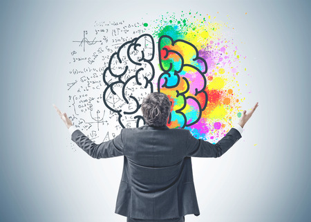 Rear view of a young successful businessman standing with hands in the air celebrating a business victory. A gray wall background with a formulae and a colorful brain sketch on it.