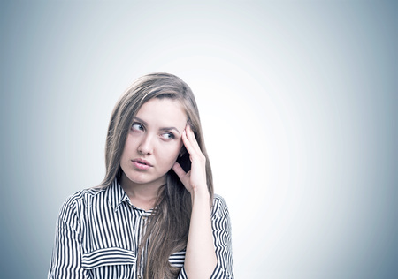 Pensive young woman wearing a striped shirt standing with her hand near the forehead and thinking. Concept of decision making. A gray wall with a mock up place