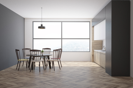 Gray kitchen interior with wooden countertops, a table with chairs and a large window. 3d rendering mock up Stock Photo