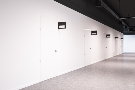 White wall office or college corridor with rows of closed doors. Mock up signposts above the doors. A concrete floor. A side view. 3d rendering 스톡 콘텐츠