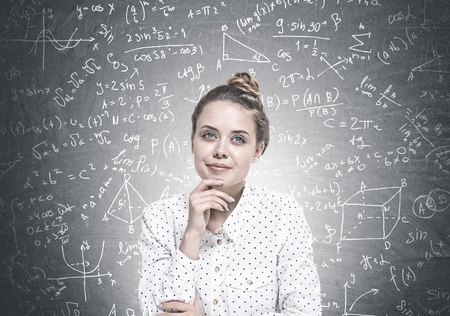 Portrait of a young woman wearing a white dotted shirt and sitting with her hand on the chin. She is looking away and dreaming. Science formula 版權商用圖片