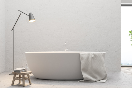 Close up of a white bathtub with a towel hanging on it standing on a concrete floor of a minimalistic bathroom. 3d rendering mock up