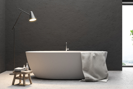 Close up of a white bathtub with a towel hanging on it standing on a concrete floor of a minimalistic black bathroom. 3d rendering mock up