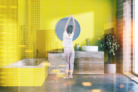 Yellow bathroom interior with a concrete floor, a yellow bathtub and a round sink standing on a wooden shelf. A round mirror. A woman. 3d rendering mock up toned image double exposure