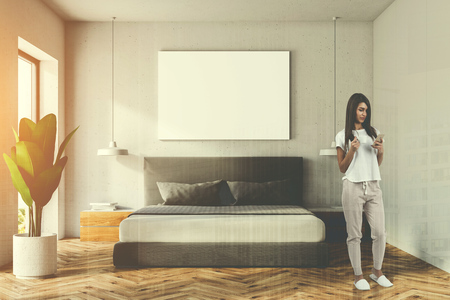 Woman in a white bedroom interior with a wooden floor, a master bed and a horizontal poster hanging above it. 3d rendering mock up toned image double exposure Stock Photo