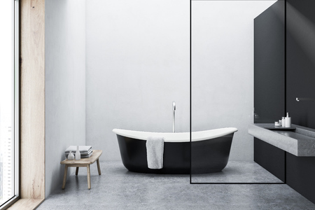 Black bathtub with a towel hanging on it standing on a concrete floor of a minimalistic gray and white wall bathroom. 3d rendering mock up Stock Photo