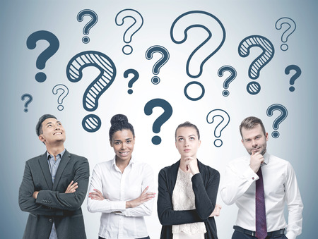 Diverse business team members standing in a row. Many blue question marks of different size drawn on a gray wall