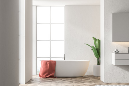 White bathtub with a red towel hanging on it standing in a modern bathroom interior with white walls. A sink to the right. 3d rendering mock up