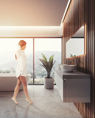 Woman in a bathroom interior with a concrete floor, a panoramic window with a mountain view and a white elegant bathtub. A double sink on a wooden wall. 3d rendering toned image