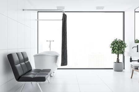 White tile bathroom interior with a white tile floor, a white bathtub and a black sofa standing near it. 3d rendering Stock Photo