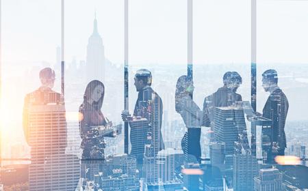 Sagome di persone d'affari in un ufficio moderno. Uno sfondo di paesaggi urbani di mattina e di notte. Concetto di lavoro di squadra Doppia esposizione tonica dell'immagine